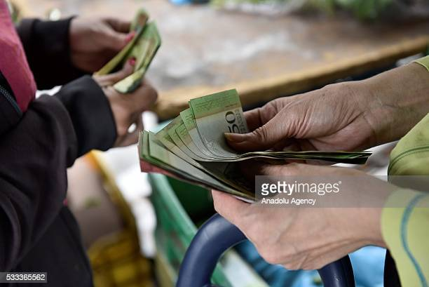 People pay for goods at a local market in Caracas Venezuela on May 21 2016 Venezuelans minimun wage is 1505115 Bs acording to the official exchange...