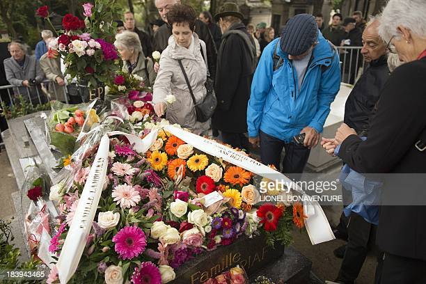 People pay respect in front of the grave of Edith Piaf at Pere Lachaise cemetery in Paris on October 10 2013 during a ceremony commemorating the 50th...