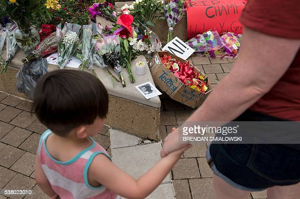 People pay respects at a makeshift memorial for boxing legend Muhammad Ali at the Muhammad Ali Center on June 4 2016 in Louisville Kentucky / AFP /...