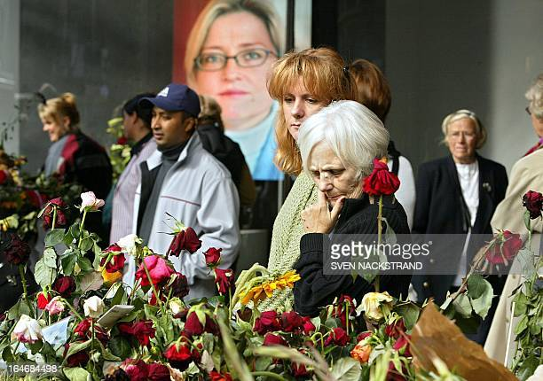People pay their respect by flowers lying outside the NK department store in Stockholm 18 September 2003 exactly a week after that Swedish Foreign...