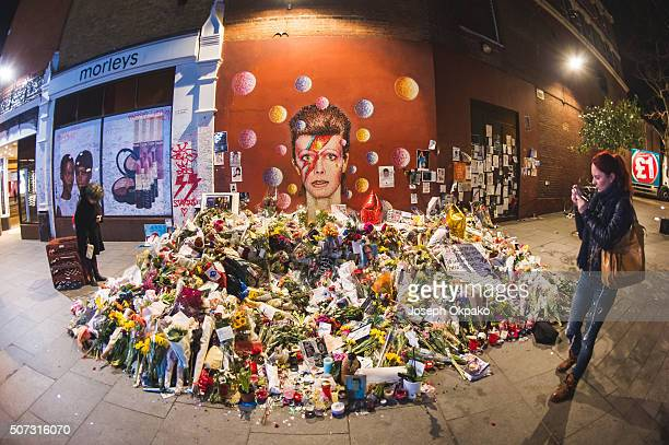 People pay their respect near the tribute mound which continues to grow two weeks after the death of Brixton born English singer songwriter David...