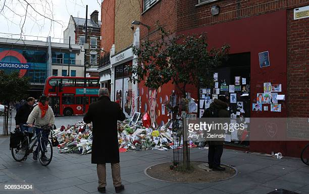 People pay their respects and photograph the flowers letters and other items left on a mound continue to grow two weeks after the death of Brixton...