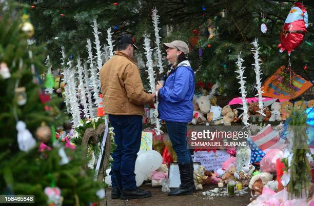 People pay their respects at a makeshift shrine to the victims of an elementary school shooting in Newtown Connecticut December 17 2012 Funerals...