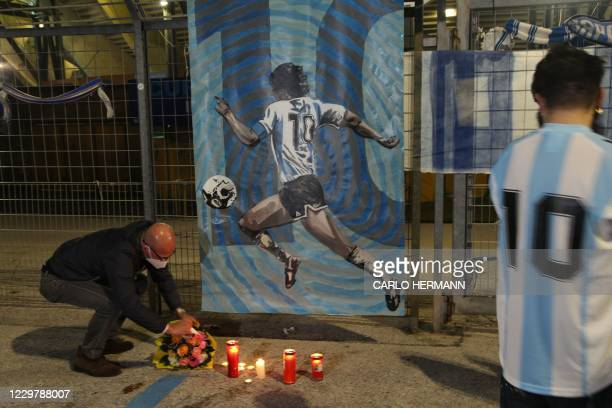People pay their respects at the main entrance of the San Paolo stadium in Naples on November 25 in front of an image of Argentinian football legend...