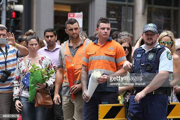 People pay their respects at the Martin Place vigil on December 16 2014 in Sydney Australia Sydney siege gunman Man Haron Monis was shot dead by...