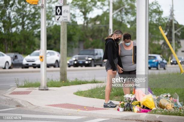 People pay their respects at the scene where a man driving a pickup truck struck and killed four members of a Muslim family in London, Ontario,...