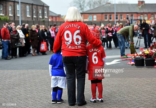 People pay their respects at the temporary Hillsborough memorial ahead of a memorial service at Anfield in Liverpool north west England on April 15...