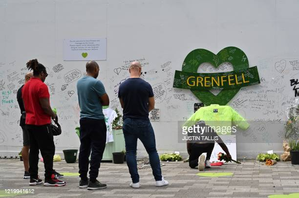 People pay their respects beside a wall where messages of support have been written surrounding Grenfell tower in west London on June 14 on the third...