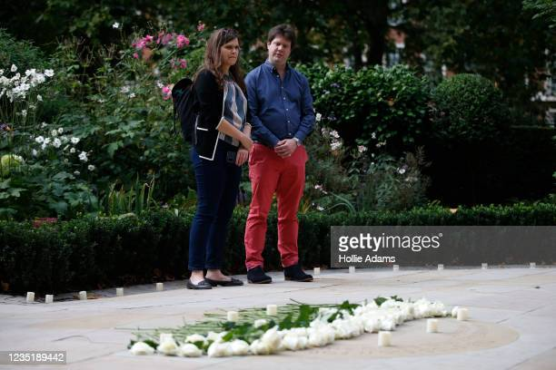 People pay their respects beside with roses laid as tributes at the September 11 Memorial Garden at Grosvenor Square on September 11, 2021 in London,...