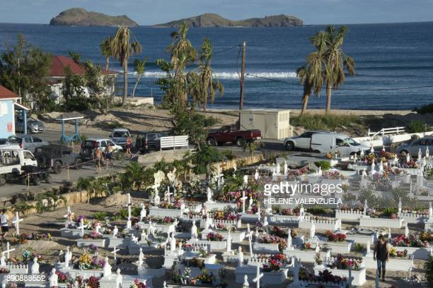 People pay their respects by the tomb of late French music icon Johnny Hallyday on the French overseas island of SaintBarthelemy on December 12 2017...