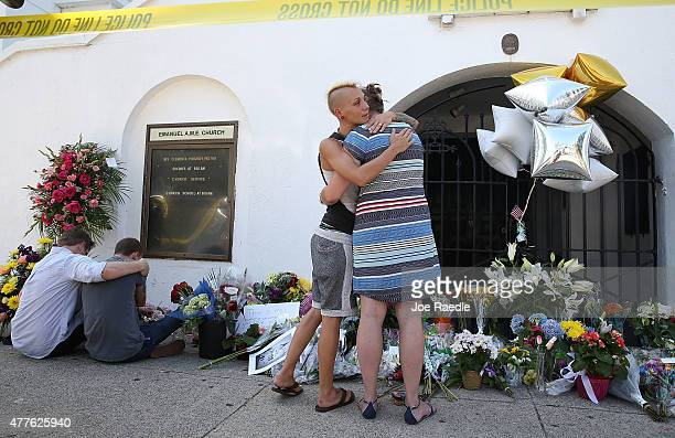 People pay their respects in front of Emanuel African Methodist Episcopal Church after a mass shooting at the church that killed nine people on June...