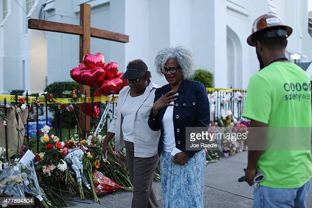 People pay their respects in front of the Emanuel African Methodist Episcopal Church after a mass shooting at the church killed nine people on June...