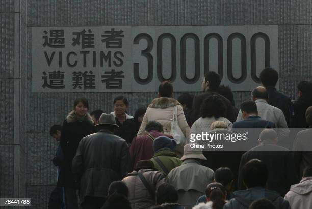 People pay their respects in front of the monument commemorating victims who died in the Nanjing Massacre of 1937 during a ceremony to mark the 70th...