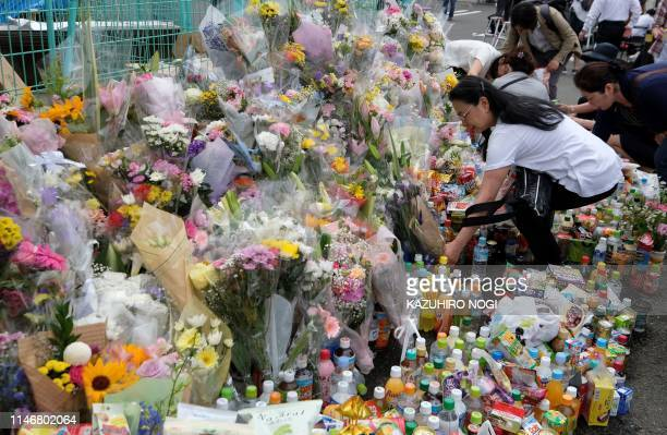 TOPSHOT People pay their respects next to flower tributes at the crime scene where a man stabbed 19 people including children in Kawasaki on May 29...