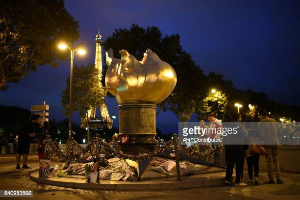 TOPSHOT People pay their respects on August 30 2017 over the Alma bridge at the Flame of Liberty monument which became an unofficial memorial for...