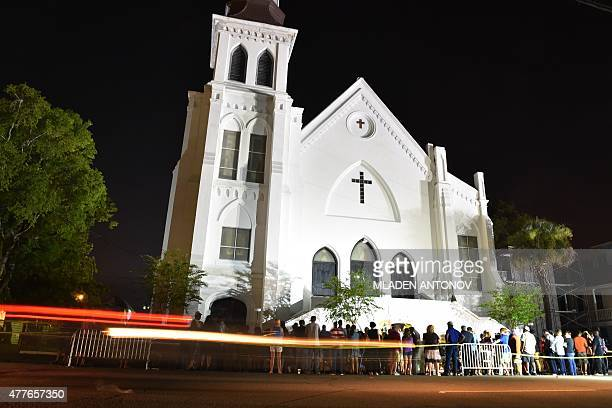 People pay their respects outside Emanuel AME Church in Charleston, South Carolina on June 18, 2015. Police captured the white suspect in a gun...