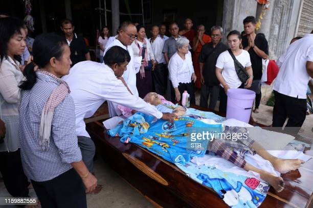 People pay their respects to Khmer Rouge 'brother number two' Nuon Chea as his wife Ly Kim Seng looks on during funeral rites at a Buddhist temple in...