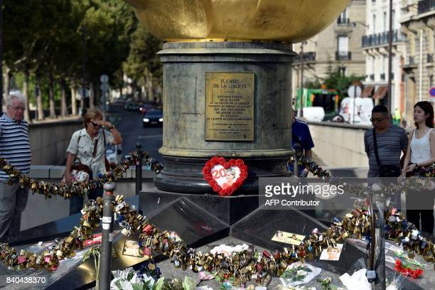 People pay their tribute to Princess Diana on August 29 in Paris around the Flame of Liberty statue plastered with iconic photos flowers and messages...