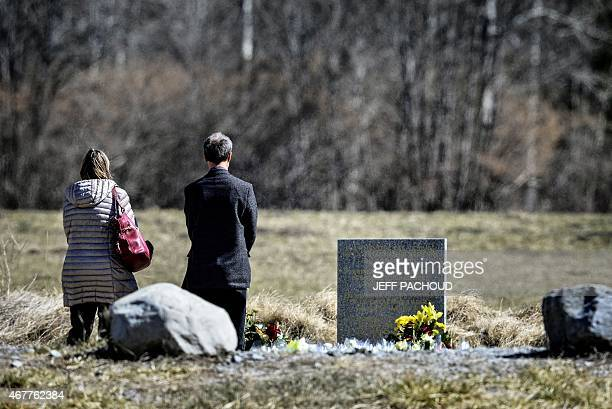 People pay tribute in front of a stele carved in French German Spanish and English in memory of the victims of the Germanwings Airbus A320 crash in...