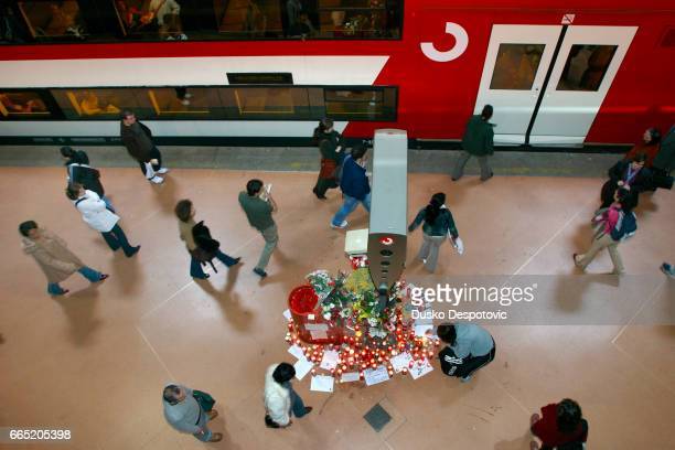 People pay tribute to the 200 victims of the March 11 terrorist attack at the Atocha train station while passengers go about their daily business as...