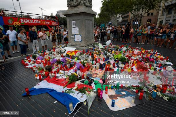 TOPSHOT People pay tribute to the victims of the Barcelona attack on Las Ramblas boulevard in Barcelona on August 19 two days after a van ploughed...