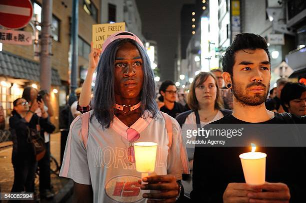 People pay tribute to victims of shooting at Pulse Nightclub in Orlando by holding banners and lighting candles on June 14 2016 at Shinjuku Nichome...