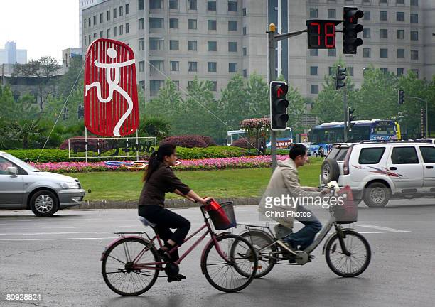 People pedal past the emblem of Beijing Olympics on the day marking the 100-day-countdown to the 2008 Olympic Games on April 30, 2008 in Nanjing of...