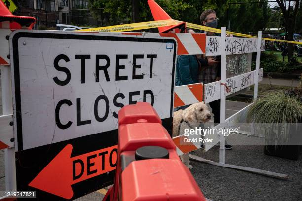"People peer through a barrier with their dog at an entrance to the so-called ""Capitol Hill Autonomous Zone"" on June 10, 2020 in Seattle, Washington...."