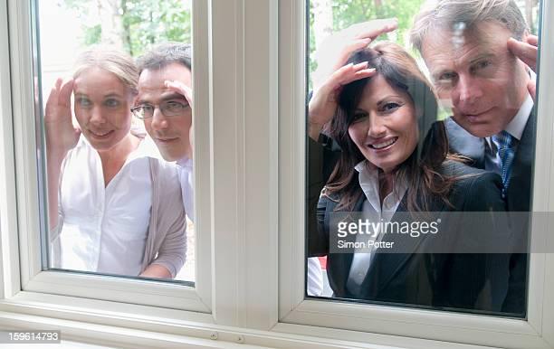 People peering in windows of house