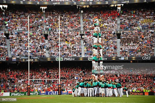 People perform a Casteller before the French Top14 rugby union final match Toulon vs Racing 92 at the Camp Nou stadium in Barcelona on June 24 2016 /...