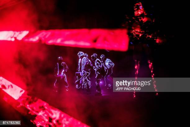 People perform a light show as part of the celebrations of the traditional event of the Sarmentelles that starts the Beaujolais Nouveau edition on...