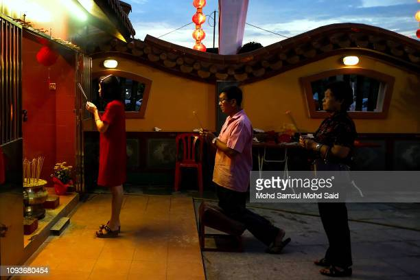 People perform a prayer inside the Kuan Yin temple on the night eve Lunar New Year of the Pig celebrations on February 4 2019 in Klang outside Kuala...