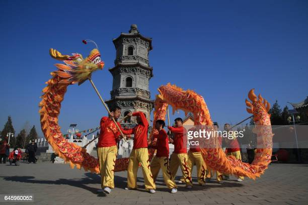 People perform dragon dance at Tiankai Temple to celebrate the Longtaitou Festival on February 27 2017 in Beijing China Chinese people eat pig's head...