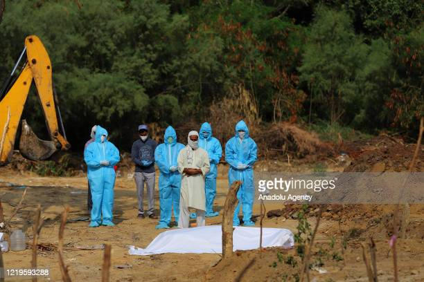 People perform funeral prayer for people who died of the novel coronavirus pandemic, at a graveyard in New Delhi, India, June 12, 2020.