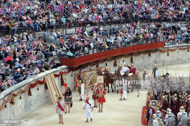People perform in the Great Roman Games show The Triumph of Cesar in the amphitheatre on May 5 2013 in Nimes southern France This event is a...