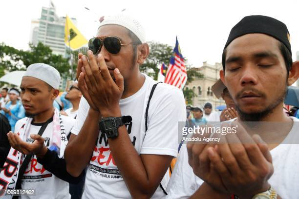 People perform prayer during the protest against the government to ratify the UN International Convention on the Elimination of All Forms of Racial...