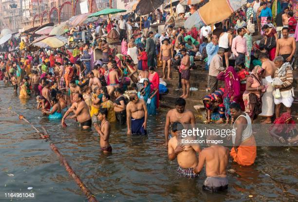 People perform ritual bath and puja prayers in the River Ganges Varanasi India