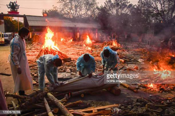 People perform the last rights of a relative who has died of Covid-19 coronavirus disease as other funeral pyres are seen burning during a mass...