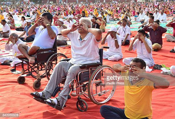 People performing yoga as they take part in a mass yoga session on the occasion of second International Yoga Day at Bikaner