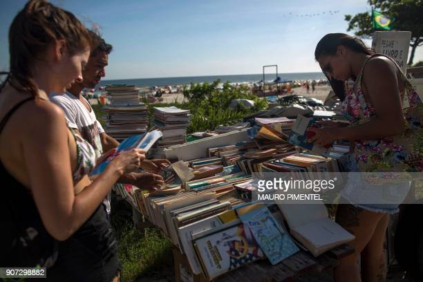 People peruse books at a booksharing stand set up by Marcio Mizael Matolias an artist who lives inside a sand castle at Barra da Tijuca beach in Rio...