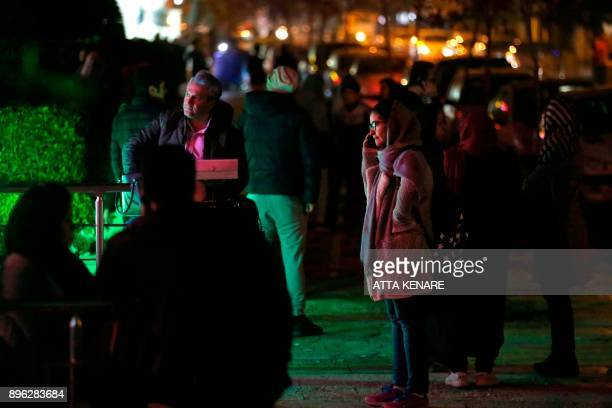People phone and wait in the streets in Tehran overnight on December 21 after an earthquake was felt in the Iranian capital The quake measuring 52...