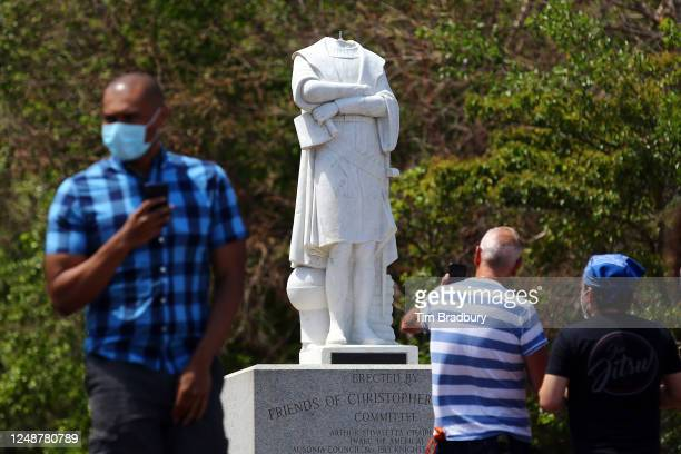 People photograph a statue depicting Christopher Columbus which had its head removed at Christopher Columbus Waterfront Park on June 10 2020 in...