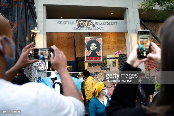 People photograph an image of activist Angela Davis displayed above the entrance to the Seattle Police Department's East Precinct vacated June 8 and...