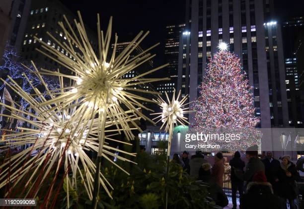 People photograph the Christmas tree in Rockefeller Center before sunrise on December 5 in New York City.