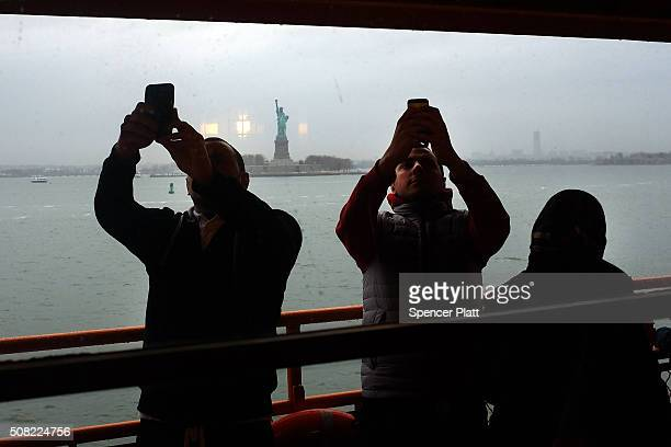 People photograph the Statue of Liberty from the deck of the Staten Island Ferry on February 3, 2016 in New York City. Following a historic blizzard...