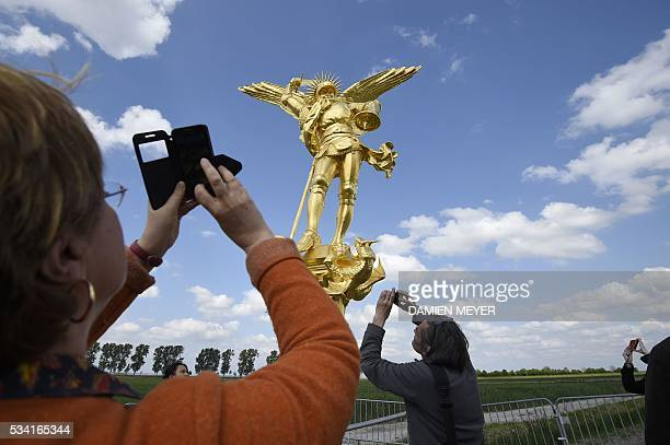 People photograph the statue of the Archangel Michael regilded and restored with a new lighting rod on the eve of its placement back atop the Mont...