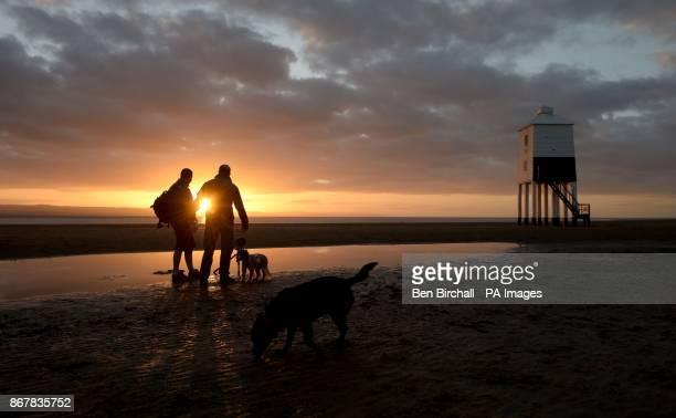 People photograph the sunset near to the lighthouse at BurnhamonSea Somerset as the sun sets an hour earlier after the clocks went back one hour last...
