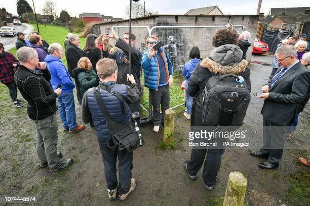 People photograph through metal fencing which has been erected to protect an artwork by street artist Banksy which has appeared on a garage wall in...