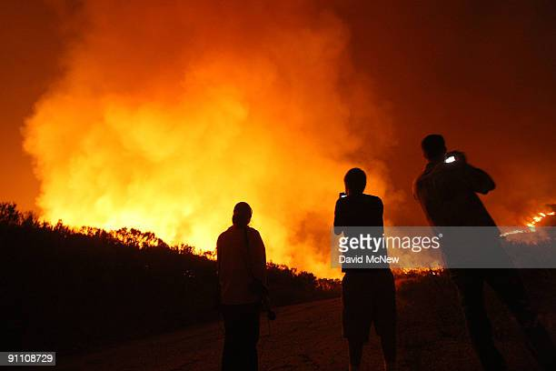 People photograph uncontrolled flames on the eastern flank of the 16000plusacre Guiberson fire burning out of control for a second day as Red Flag...