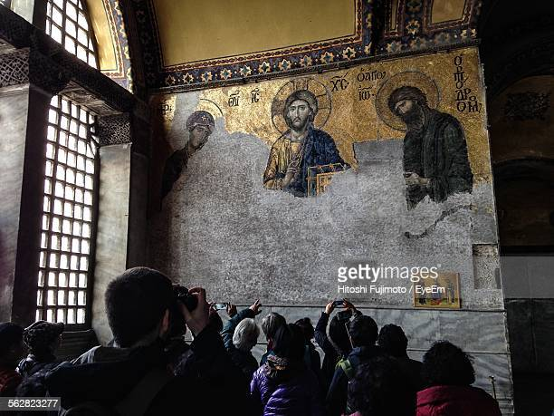 People Photographing Christian Mosaics On Wall In Hagia Sophia